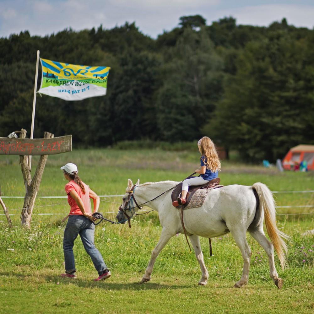 Een wit paard met een meisje erop en een vrouw ernaast, wandelend over de camping