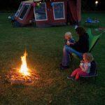 Een moeder met twee kinderen op een stoeltje bij het kampvuur