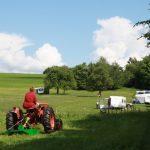 Een rode traktor maait het gras op Farm Camp Lazy Slowakije