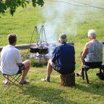 Een vuur met kookpotten er boven en drie gasten erbij