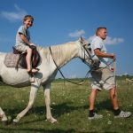 Een jongen op een wit paard en de boer die er mee wandelt
