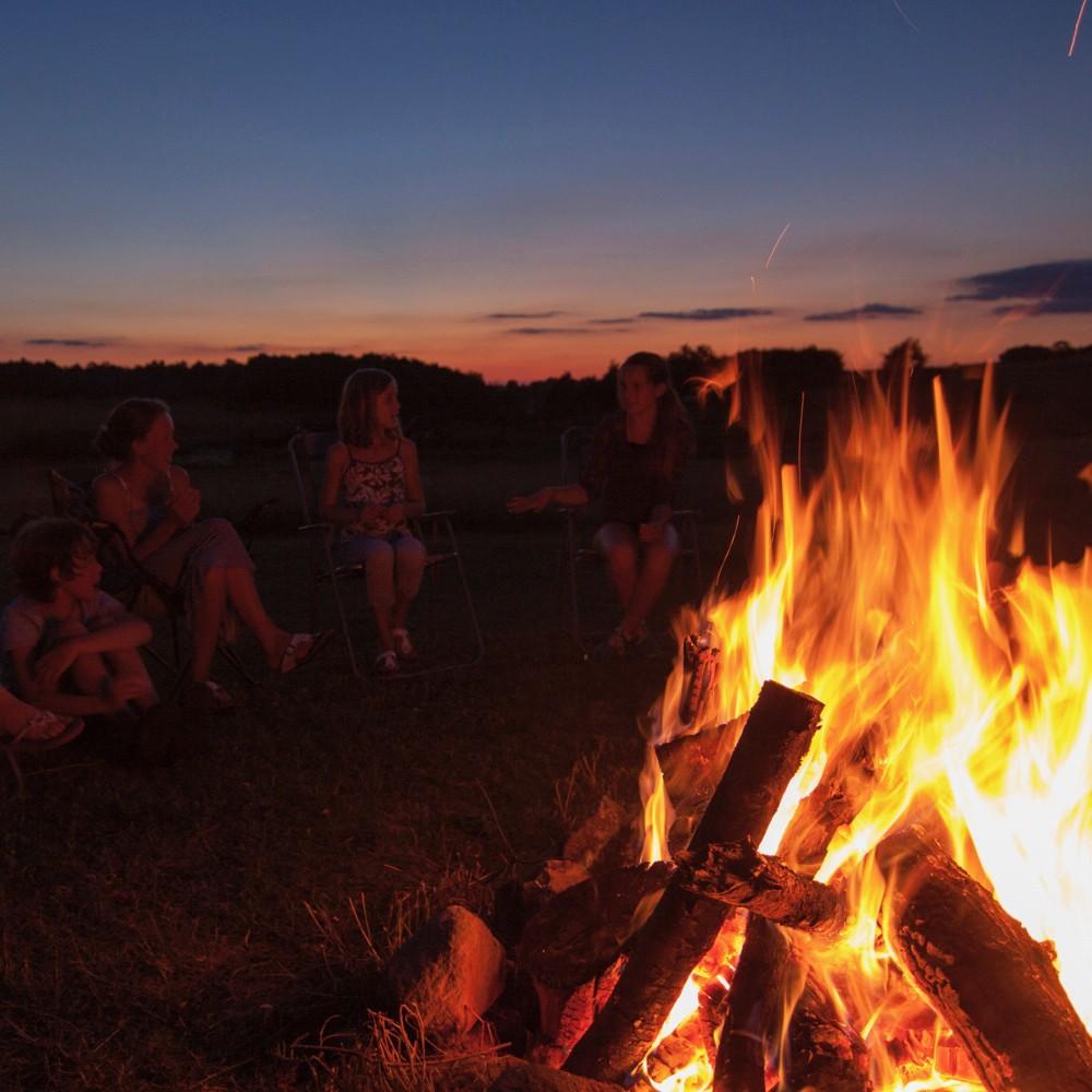 Kampvuur en avondrood, mensen genieten bij het vuur