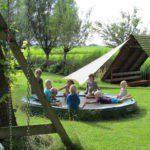 Op de trampoline zitten kinderen in een kring, naast de overdekte kampvuurplek.