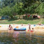 Zwemmeer met strandje en spelende kinderen