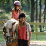 Een klein meisje op een pony, begeleid door een groter meisje