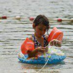 Een meisje in het water met vleugeltjes en een zwemband om.
