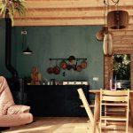 Een zelfgebouwde accommodatie met veel hout, leren fauteuil en groene muur