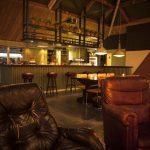 De bar van Camping BuitenLand met vintage leren fauteuils en ouderwetse barkrukken.