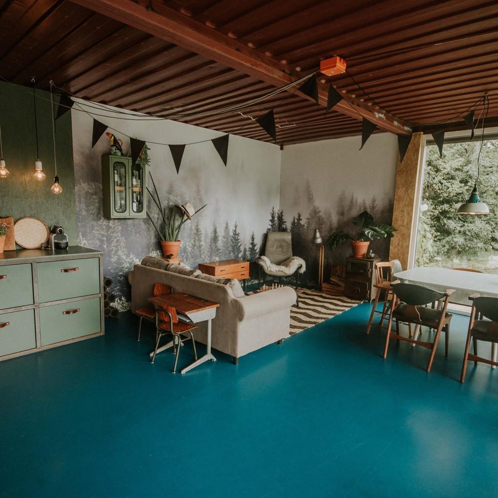Interieur van De Wildernis, met een blauwe vloer, tafel met stoelen en een beige bank