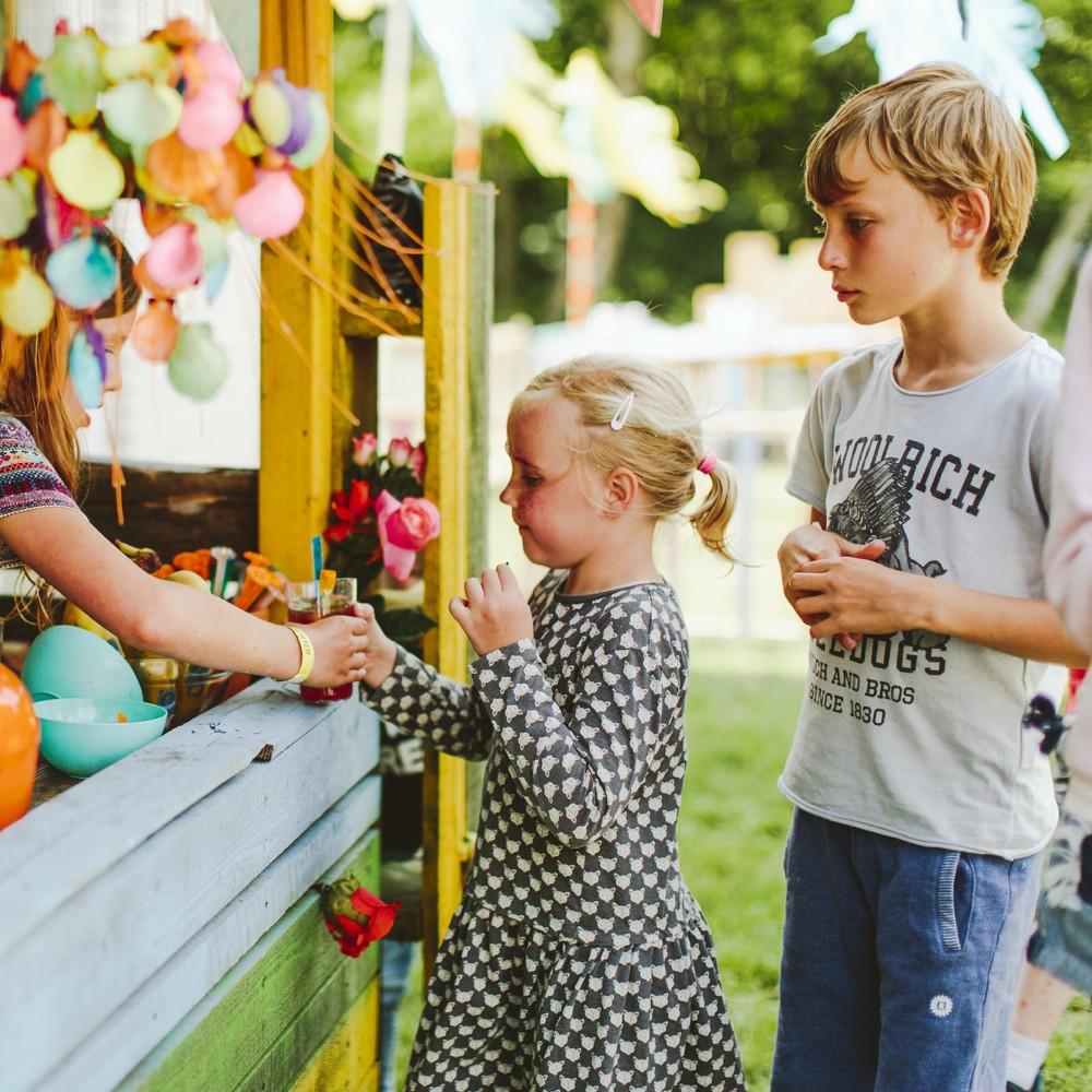 Een meisje en jongen voor een snoepkraam op de camping