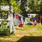 Een mintgroene caravan met een vlaggetjes lijn op Camping BuitenLand