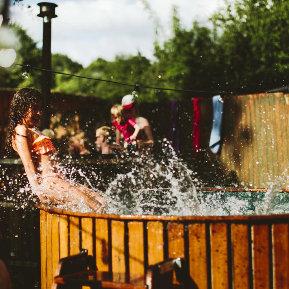 Een houten hot tub waar de spetters uit vliegen en een spelend kind er in, op Camping BuitenLand