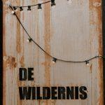 Een rij lampjes op een oude houten deur en de letters De Wildernis.