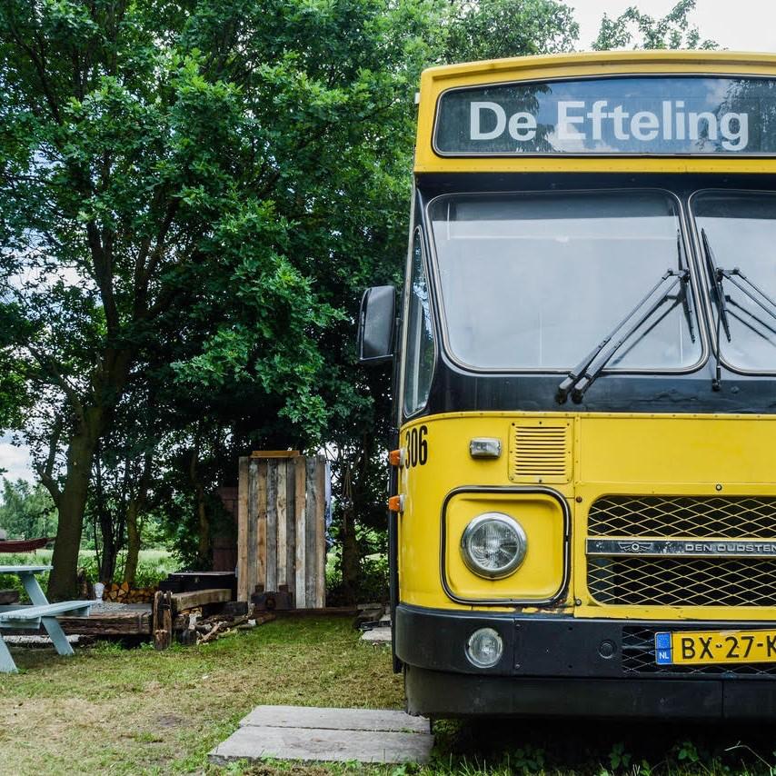 Een oude gele bus met als bestemming de Efteling, nu te reserveren als accommodatie op Camping BuitenLand