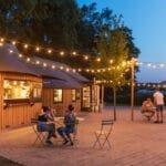 Terras met gezellige lampjes bij Camping Huttopia de Roos in Overijssel