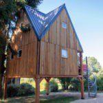 Een houten boomhut op palen, met spits dak
