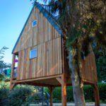 Een houten boomhuut met spits dak