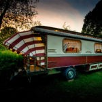 Een ouderwetse rood-witte zigeunerwagen met balkon.