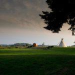 Een groen kampeerveld met in de verte een grote tipi tent en een wijnvat.