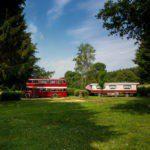 Een rode dubbeldekker en een grote woonwagen op een ruim groen kampeerveld.