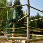 Een klimrek van grote houten palen met touwen en net.