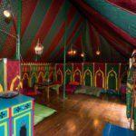 De Marokkaanse tent van binnen, met een houten vloertje en sfeervol groen-rood gekleurd tentdoek.