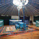 De blauwe yurt van binnen, met traditionele Mongools beschilderde meubels en in het midden van het dak een ronde lichtkoepel