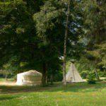 Een yurt en een tipi op het gras, onder de bomen.