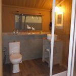 Een toilet, wastafel en douchecabine in een safaritent
