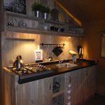 Een steigerhouten keuken bij avondlicht in een safaritent