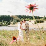 Een kussend bruidspaar tussen de veldbloemen en een zwemvijver als achtergrond