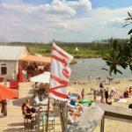 Een strandpaviljoen met gasten en zwemmende gasten
