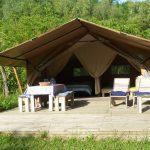 Vooraanzicht van een safaritent met eettafel en ligstoelen op de veranda