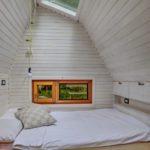 Een tweepersoons bed in een wit geschilderd houten design huis met dakraam