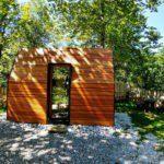Een houten design huis onder bomen