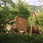 Een verfijnd houten huisje in het groen, met design ligbanken voor de deur.