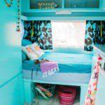 De slaaphoek van een gepimpte caravan met lichtblauwe kleuren