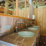 Drie wastafels op een rij met spiegels erboven in het sanitairgebouw van Kamp Koren