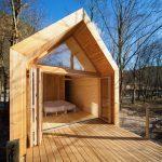 Tiny House, modern van hout, met grote openslaande deuren waardoor je op het bed kijkt
