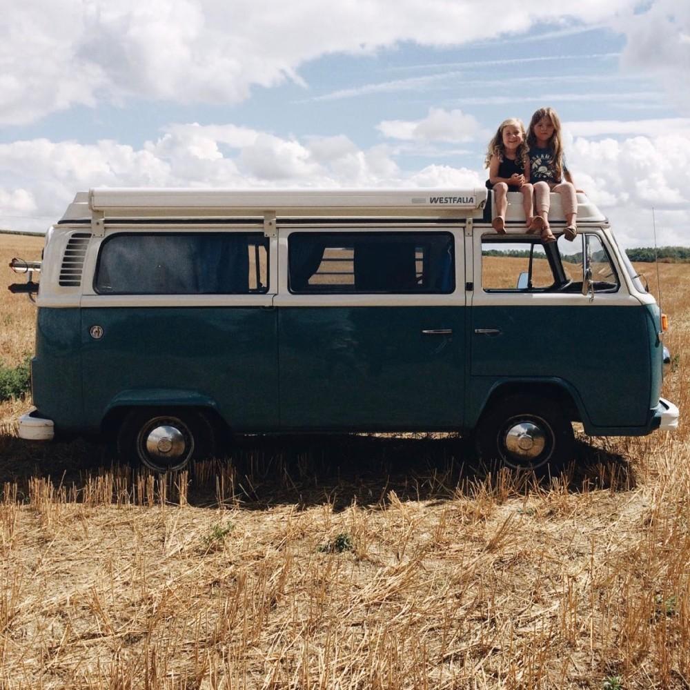 Een volkswagen busje in een korenveld, met twee kinderen op het dak