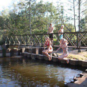 Twee kinderen springen met opgetrokken knieën van een bruggetje in de rivier.