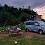 Volkswagen camper met gekleurde slinger en picknicktafel