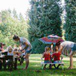 kleine kinderen aan twee picknicktafels in het gras.