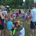 Een grote groep kinderen rond het kampvuur met stokken en marshmellows