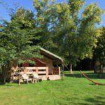 Safaritent met veranda op het groene gras onder de bomen.