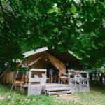 Een grote safaritent met houten veranda, onder de bomen.