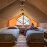 Twee eenpersoonsbedden op de 1e etage van een lodge tent, met een raam aan de achterzijde