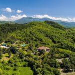 Glooiend groen heuvellandschap van bovenaf met daar midden in het zwembad en Casale il Sogno.