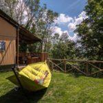 Een grote hangmat bij een lodge-tent met uitzicht over de heuvels.