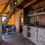 De houten keuken in de lodgetent en de trap naar de eerste etage.